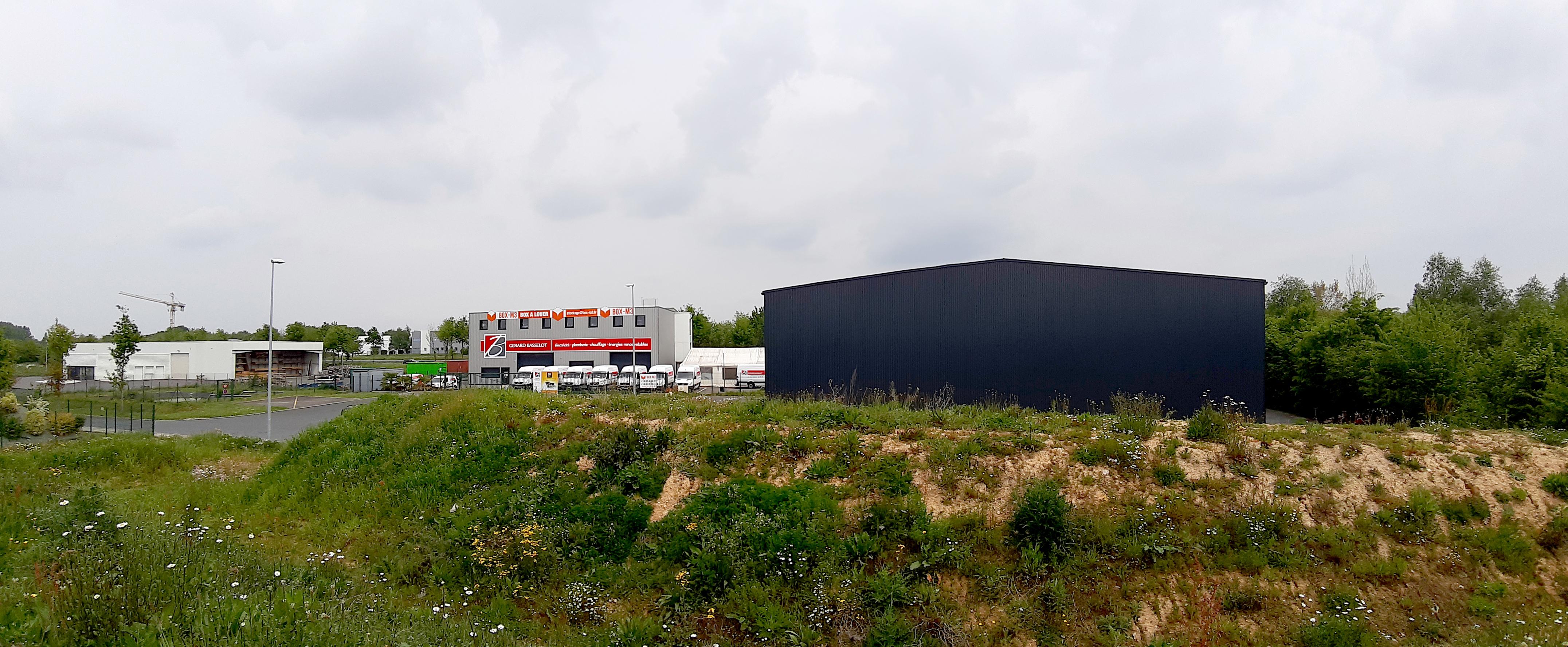 Dans une zone artisanale, aux constructions héteroclites, le nouveau bâtiment joue la sobriété. Le volume très simple et compact est voulu, et rendu possible par l'intégration à l'intérieur de l'enveloppe des bureaux et de l'entrée.