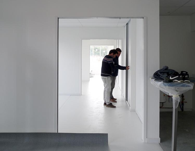 Une allée centrale dessert tous les bureaux individuels ou partagés. Lorsque les larges portes coulissantes sont toutes ouvertes, l'ensemble devient un plateau libre avec des alcôves.